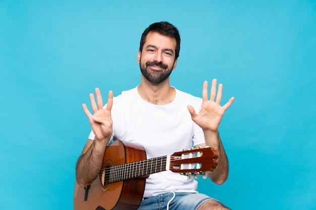 Junger mann mit gitarre über dem lokalisierten blau, das neun mit den fingern zählt