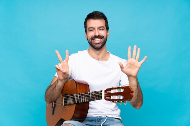 Junger mann mit gitarre über dem lokalisierten blau, das sieben mit den fingern zählt