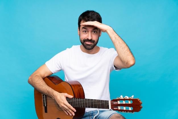 Junger mann mit gitarre über dem lokalisierten blau, das weit weg mit der hand schaut, um etwas zu schauen
