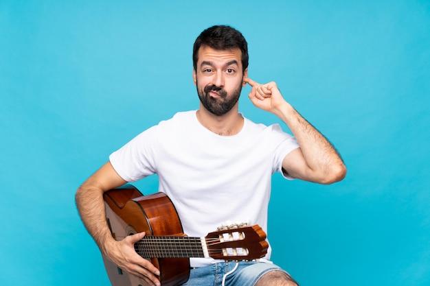 Junger mann mit gitarre über den blauen frustrierten und bedeckungsohren