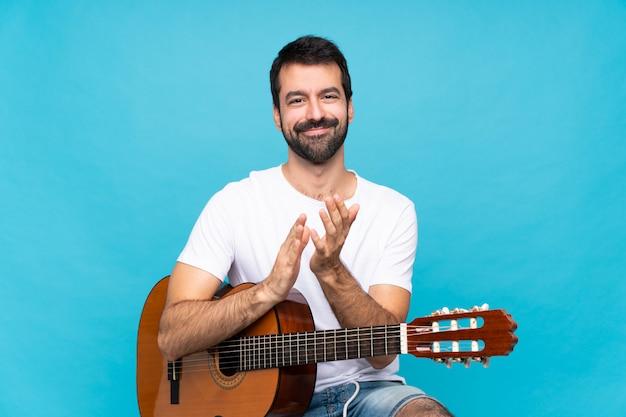 Junger mann mit gitarre über der lokalisierten blauen wand, die nach darstellung in einer konferenz applaudiert