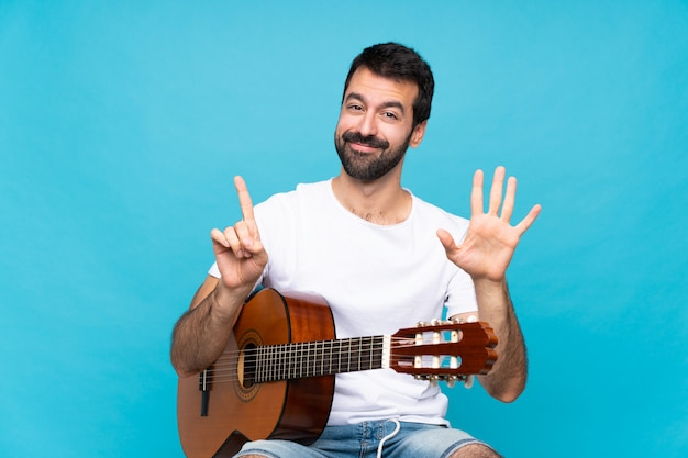 Junger mann mit gitarre über der lokalisierten blauen wand, die sechs mit den fingern zählt