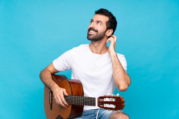 Junger mann mit gitarre über getrenntem blau eine idee denkend