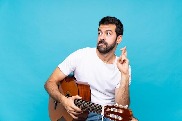 Junger mann mit gitarre über getrenntem blau mit den fingern, die das beste kreuzen und wünschen