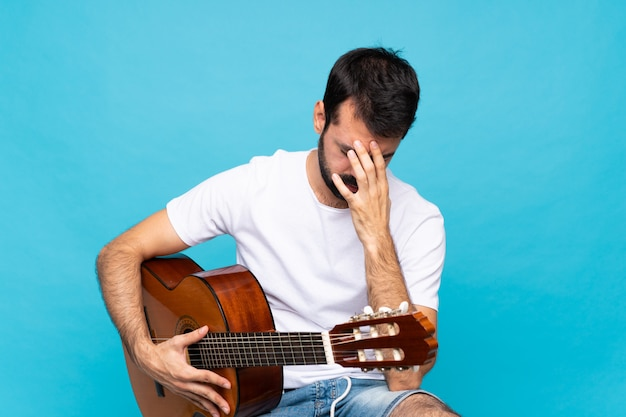 Junger mann mit gitarre über getrenntem blau mit müdem und krankem ausdruck