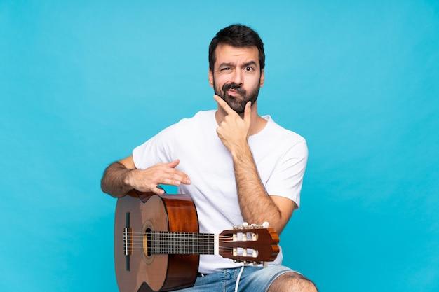 Junger mann mit gitarre über getrenntem blauem denken