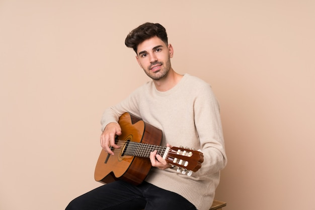 Junger mann mit gitarre über getrenntem hintergrund