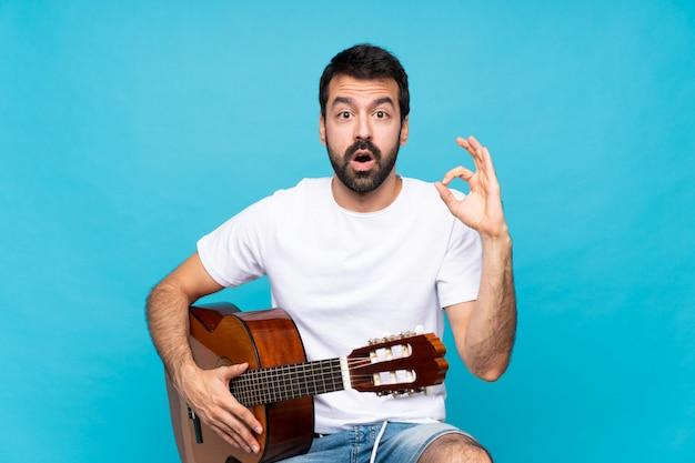 Junger mann mit gitarre über lokalisiertem blau überrascht und okayzeichen zeigend