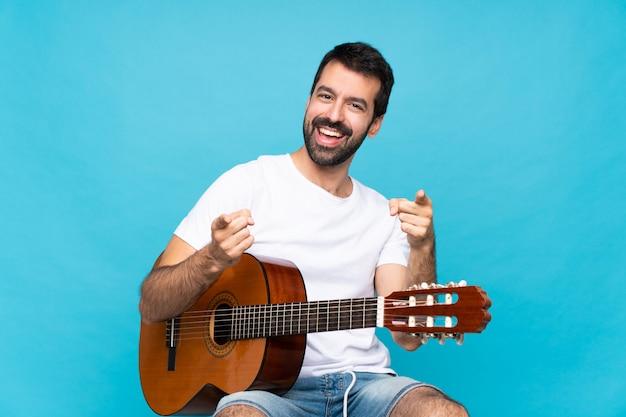 Junger mann mit gitarre über lokalisiertem blau zeigt finger auf sie beim lächeln