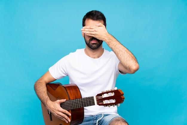 Junger mann mit gitarre über lokalisierten blauen bedeckungsaugen durch hände, möchten nicht etwas sehen