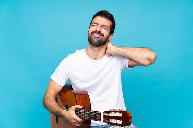 Junger mann mit gitarre über lokalisierter blauer wand mit halsschmerzen