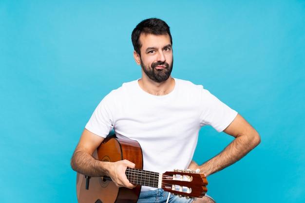 Junger mann mit gitarre über lokalisierter blauer wand verärgert