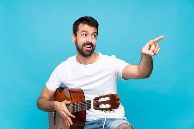 Junger mann mit gitarre weg zeigend