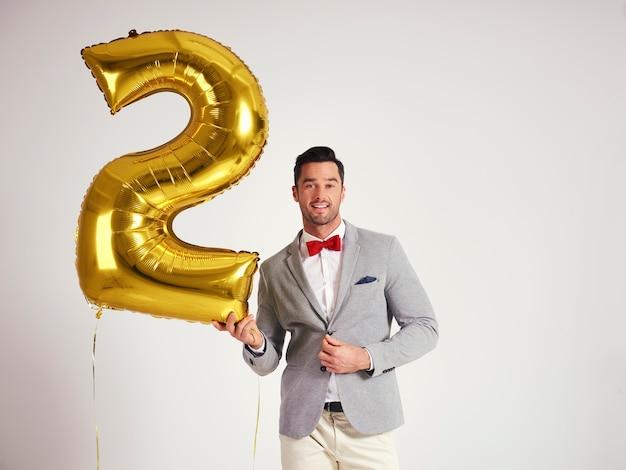 Junger mann mit goldenem ballon, der zweiten geburtstag seiner firma feiert