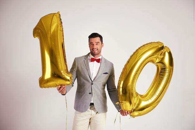 Junger mann mit goldenem ballon in 10 form