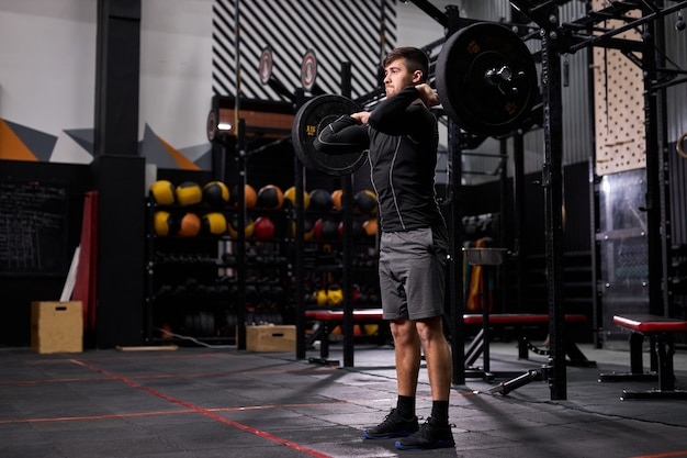 Junger mann mit großen muskeln, die schweres gewicht für cross-fit-swing-training mit hartem kerntraining im fitnessstudio halten und allein sportliche kleidung tragen. porträt