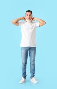 Junger mann mit halskragen am hals gegen farbe