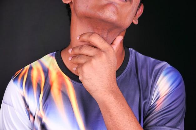 Junger mann mit halsschmerzen auf schwarzem hintergrund