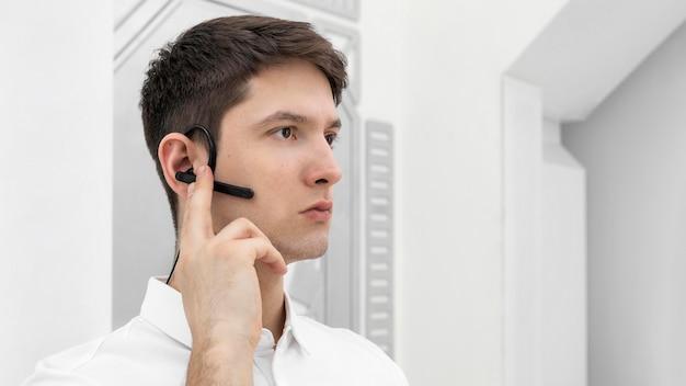 Junger mann mit handprototyp, der bluetooth-kopfhörer aktiviert