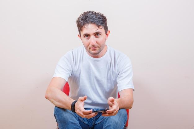 Junger mann mit handy beim sitzen auf stuhl in t-shirt, jeans