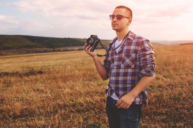 Junger mann mit hippie-lebensstil der retro- fotokamera im freien