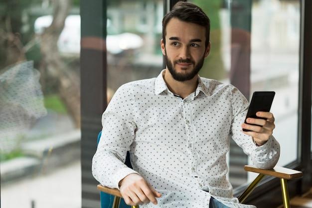 Junger mann mit hohem winkel, der mobil hält