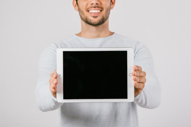 Junger mann mit horizontaler tablette