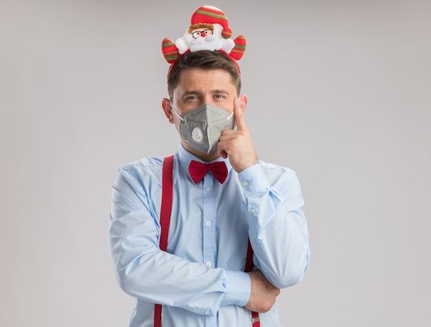 Junger mann mit hosenträgerfliege in rand mit weihnachtsmann mit schützender gesichtsmaske, der die kamera mit ernstem, selbstbewusstem ausdruck auf weißem hintergrund anschaut
