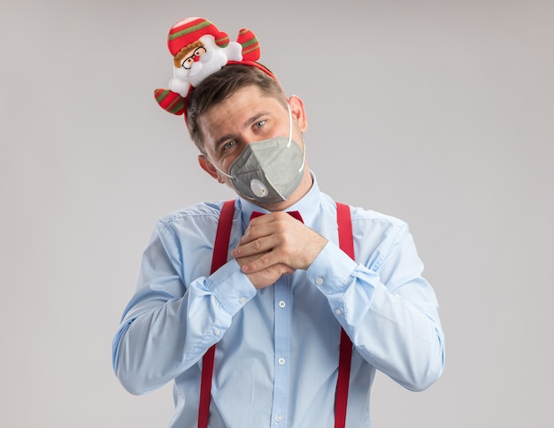Junger mann mit hosenträgerfliege in rand mit weihnachtsmann mit schützender gesichtsmaske und blick in die kamera mit glücklichem gesicht, das die hände zusammenhält, die auf weißem hintergrund stehen