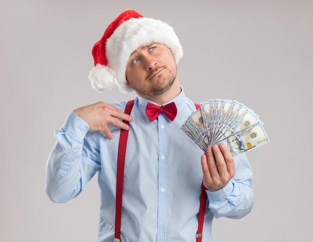 Junger mann mit hosenträgerfliege in weihnachtsmütze mit bargeld, der verwirrt auf weißem hintergrund aufschaut