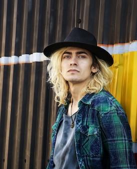 Junger mann mit hut, der an einer gelben und schwarzen wand in die kamera schaut