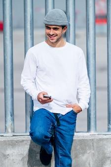 Junger mann mit hut unter verwendung des mobiltelefons