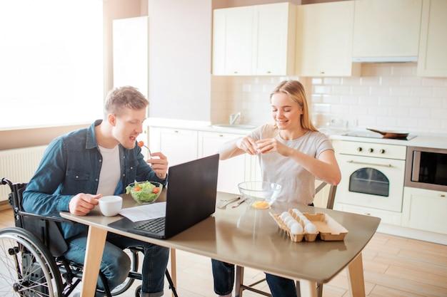 Junger mann mit inklusivität und besonderen bedürfnissen, der salat in der küche isst. setzen sie sich auf einen rollstuhl und lernen sie. junge frau sitzt daneben und bricht eier. zusammen arbeiten.