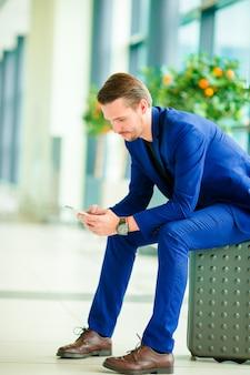 Junger mann mit intelligentem telefon im flughafen. kaukasischer mann mit mobiltelefon am flughafen beim warten auf einstieg