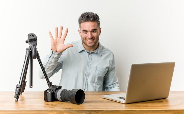 Junger mann mit kamera und laptop