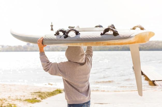Junger mann mit kitesurfbrett