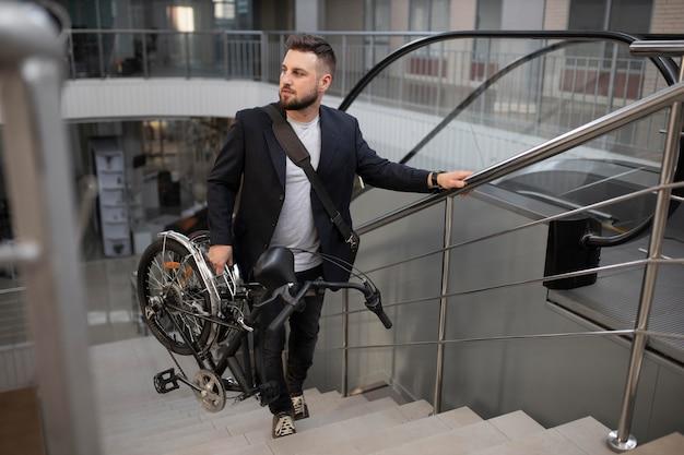 Junger mann mit klapprad auf rolltreppe