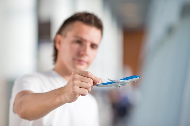 Junger mann mit kleinem flugzeug im flughafen, der seinen flug wartet