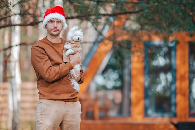 Junger mann mit kleinem hund im weihnachtsmannhintergrund des hauses