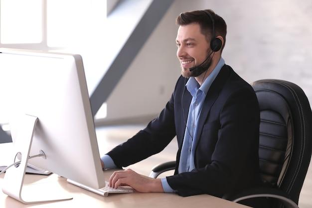 Junger mann mit kopfhörer, der im büro arbeitet