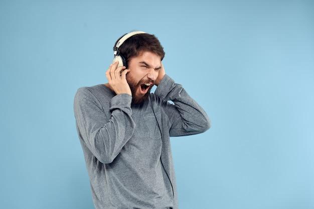 Junger mann mit kopfhörern an einer hellblauen wand