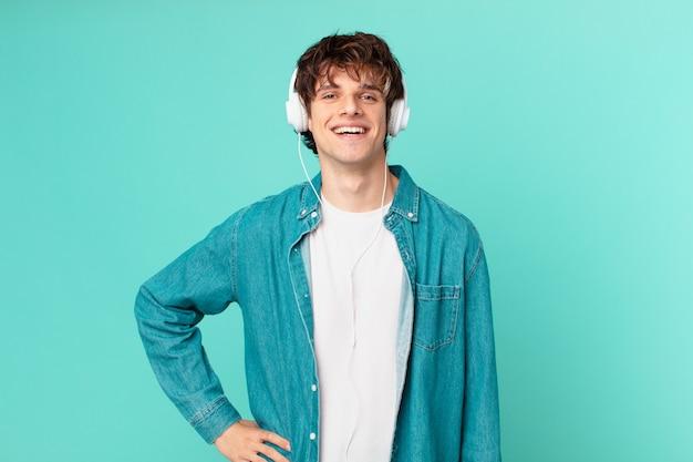 Junger mann mit kopfhörern, der glücklich mit einer hand auf der hüfte und selbstbewusst lächelt