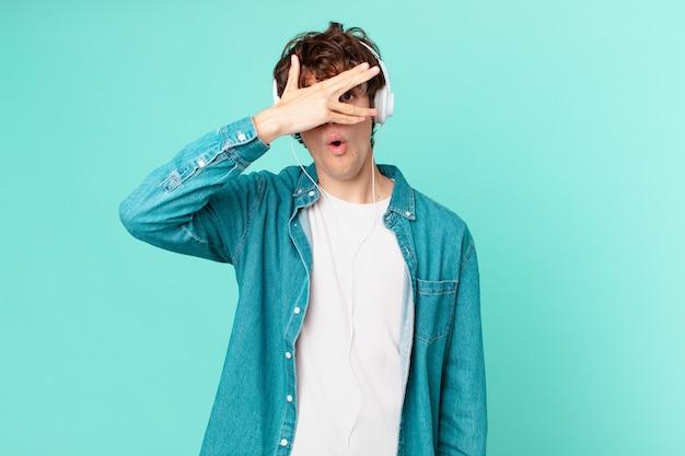 Junger mann mit kopfhörern, der schockiert, verängstigt oder verängstigt aussieht und das gesicht mit der hand bedeckt