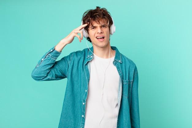 Junger mann mit kopfhörern, der sich verwirrt und verwirrt fühlt und zeigt, dass sie verrückt sind