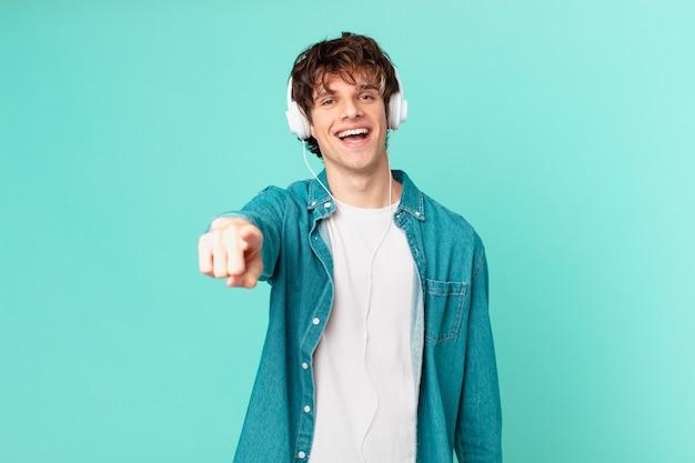 Junger mann mit kopfhörern, die auf die kamera zeigen, die dich auswählt