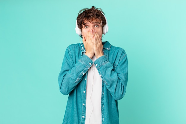 Junger mann mit kopfhörern, die den mund mit den händen mit einem schockierten bedecken