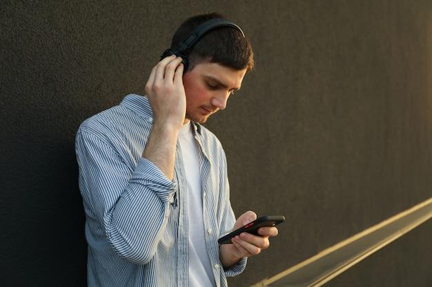 Junger mann mit kopfhörern hört musik
