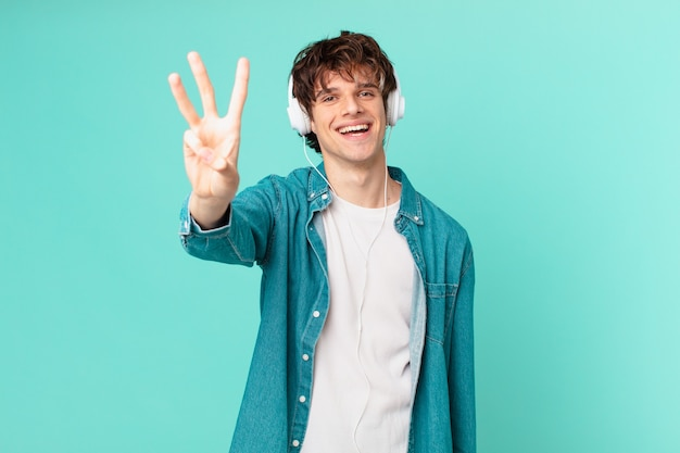 Junger mann mit kopfhörern lächelt und sieht freundlich aus und zeigt nummer drei