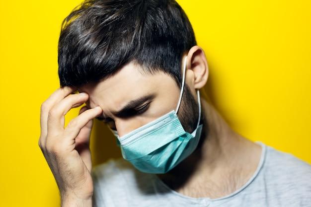 Junger mann mit kopfschmerzen, hand auf kopf haltend, medizinische grippemaske auf gelber wand tragend.