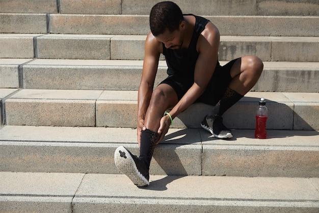 Junger mann mit krämpfen nach dem training